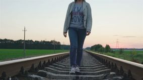 Young beautiful trendy woman walking on railroad track. Railroad ties and stone with traveling girl. Summer season stock video footage