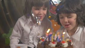 Young beautiful twin sisters blowing candles on a birthday cake, slow motion stock video footage