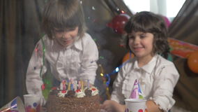 Young beautiful twin sisters blowing candles on a birthday cake, slow motion. Young beautiful twin sisters blowing candles on a birthday cake in slow motion stock video