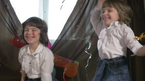Young beautiful twin sisters dancing at a birthday party with confetti, slow motion. Young beautiful twin sisters dancing at a birthday party with confetti in stock video footage
