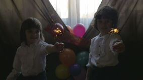 Young beautiful twin sisters playing with fireworks at a birthday party, slow motion stock video footage