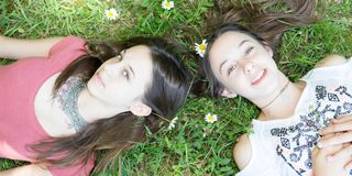 Young beautiful twins girl sister lays on field. Young beautiful twins girl sister lays on green field royalty free stock photography