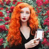 Young beautiful unusual redhead girl with very long curly hair on a background of a bush of red roses. royalty free stock photo