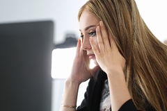 Young beautiful upset business woman trying to concentrate. Looking at laptop monitor Royalty Free Stock Photography