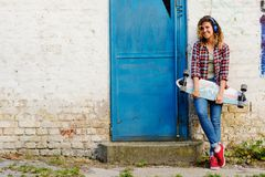 Young beautiful urban skate girl holding long-board in the street Stock Photo