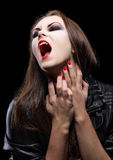Young beautiful vampire woman. On black Stock Photography