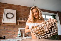 A young beautiful welcoming girl at home standing in loft kitchen smiling carrying a basket of hand made bread just cooked. A young beautiful standing at home in stock image