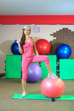 Young beautiful white girl in cap and pink sports suit does physical exercises with dumbells and fit ball at the fitness center. Royalty Free Stock Photos