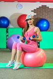 Young beautiful white girl in cap and pink sports suit does physical exercises with dumbells and fit ball at the fitness center. Royalty Free Stock Image
