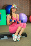 Young beautiful white girl in a pink sports suit does physical exercises with dumbbells at the fitness center. Royalty Free Stock Images