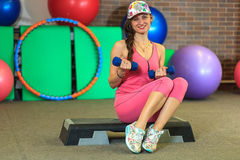 Young beautiful white girl in a pink sports suit does physical exercises with dumbbells at the fitness center. Royalty Free Stock Photo