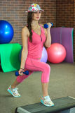 Young beautiful white girl in a pink sports suit does physical exercises with dumbbells at the fitness center. Stock Photography