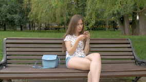 Young beautiful white girl is sitting on a park bench. Listens to music on the smartphone. Sings melodies. Cloudy day stock video