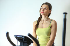 Young beautiful white girl in a yellow and gray sports suit is engaged on a stationary bike in the fitness club. Fitness. Young beautiful white girl in a yellow Stock Images