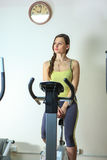 Young beautiful white girl in a yellow and gray sports suit is engaged on a stationary bike in the fitness club. Fitness. Young beautiful white girl in a yellow Royalty Free Stock Images