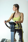 Young beautiful white girl in a yellow and gray sports suit is engaged on a stationary bike in the fitness club. Fitness. Young beautiful white girl in a yellow Royalty Free Stock Image