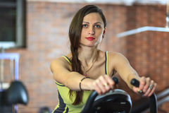 Young beautiful white girl in a yellow and gray sports suit is engaged on a stationary bike in the fitness club. Fitness. Young beautiful white girl in a yellow Stock Photography