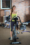 Young beautiful white girl in a yellow and gray sports suit is engaged on a stationary bike in the fitness club. Stock Photos