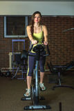 Young beautiful white girl in a yellow and gray sports suit is engaged on a stationary bike in the fitness club. Royalty Free Stock Image