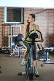 Young beautiful white girl in a yellow and gray sports suit is engaged on a stationary bike in the fitness club. Stock Image