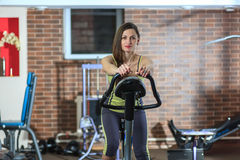 Young beautiful white girl in a yellow and gray sports suit is engaged on a stationary bike in the fitness club. Royalty Free Stock Photography