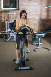 Young beautiful white girl in a yellow and gray sports suit is engaged on a stationary bike with smartphone in the fitness club. Royalty Free Stock Photos