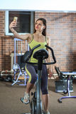 Young beautiful white girl in a yellow and gray sports suit is engaged on a stationary bike with smartphone in the fitness club. Stock Image