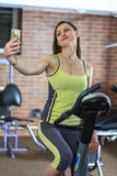 Young beautiful white girl in a yellow and gray sports suit is engaged on a stationary bike with smartphone in the fitness club. Stock Images