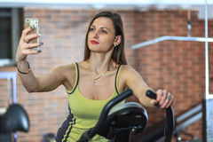 Young beautiful white girl in a yellow and gray sports suit is engaged on a stationary bike with smartphone in the fitness club. Fitness selfie. Young beautiful Royalty Free Stock Photo