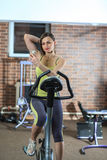 Young beautiful white girl in a yellow and gray sports suit is engaged on a stationary bike with smartphone in the fitness club. Fitness selfie. Young beautiful Stock Image