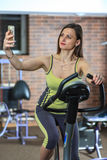 Young beautiful white girl in a yellow and gray sports suit is engaged on a stationary bike with smartphone in the fitness club. Fitness selfie. Young beautiful Royalty Free Stock Photos