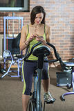 Young beautiful white girl in a yellow and gray sports suit is engaged on a stationary bike with smartphone in the fitness club. Fitness selfie. Young beautiful Stock Photography