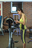 Young beautiful white girl in a yellow and gray sports suit thought before a workout at the fitness club. Royalty Free Stock Photo