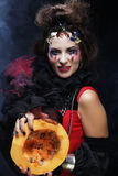 Young beautiful witch holding a pumpkin  over dark background Stock Photos