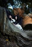 Young beautiful witch with long dark hair in root of old tree Stock Image