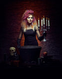 Young and beautiful witch making witchcraft in the dungeon Royalty Free Stock Images