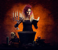 Young and beautiful witch making witchcraft in the dungeon. Young and beautiful witch making a witchcraft in dungeon. Halloween composition Royalty Free Stock Photography