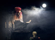 Young and beautiful witch making witchcraft in the dungeon Stock Image