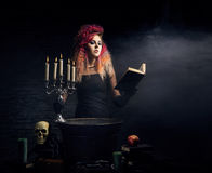 Young and beautiful witch making witchcraft in the dungeon. Young and beautiful witch making a witchcraft in dungeon. Halloween composition Royalty Free Stock Images