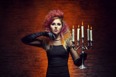 Young and beautiful witch making witchcraft. Young and beautiful witch making a witchcraft in dungeon. Halloween composition Royalty Free Stock Photo