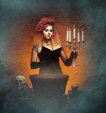 Young and beautiful witch making witchcraft. Young and beautiful witch making a witchcraft in dungeon. Halloween composition Royalty Free Stock Photos