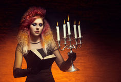 Young and beautiful witch making witchcraft. Young and beautiful witch making a witchcraft in dungeon. Halloween composition Royalty Free Stock Images