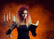 Young and beautiful witch making witchcraft. Young and beautiful witch making a witchcraft in dungeon. Halloween composition Stock Photos