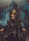 Young beautiful witch sits on a chair. Bright make up, skull, smoke-  halloween theme. Stock Photos