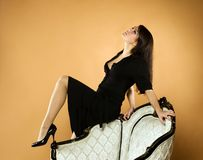 Young beautiful woman. Posing at antique armchair Royalty Free Stock Images