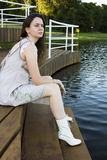 Young beautiful woman. Sitting on wooden deck stock image