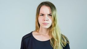 Young beautiful woman is angry on a white background. Angry young woman. Slow motion.  stock footage