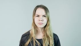 Young beautiful woman is angry on a white background. Angry young woman.  stock footage
