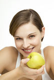 Young beautiful woman with apple. Young beautiful woman with an apple looking towards camera Royalty Free Stock Photos