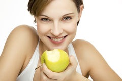 Young beautiful woman with apple. Young beautiful woman with an apple looking towards camera Royalty Free Stock Photo